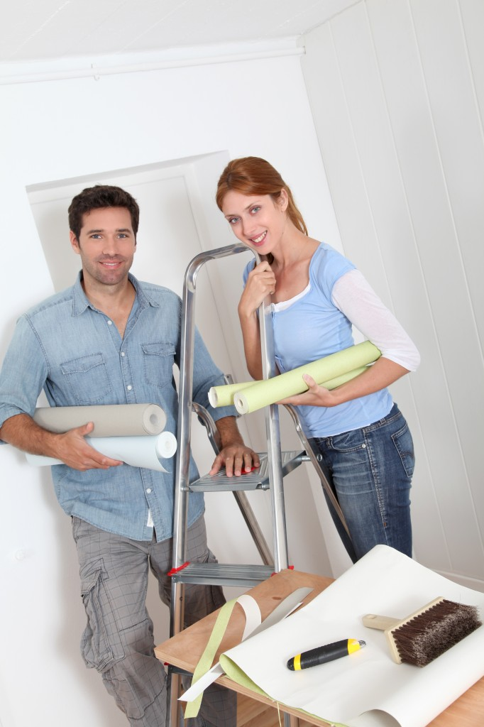 Couple putting new wallpaper in room