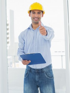 Portrait of a smiling young architect in yellow hard hat with clipboard gesturing thumbs up in a bright office